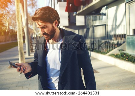 Portrait of handsome adult man sending a text message while standing in the city street,business man reading messages,stylish brunette hipster using cell phone at sunny evening outdoors,flare sunshine - stock photo
