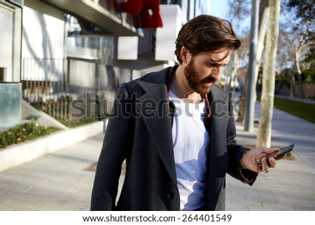 Portrait of handsome adult man sending a text message while standing in the city street, business man reading messages, stylish brunette hipster using cell phone at sunny evening outdoors
