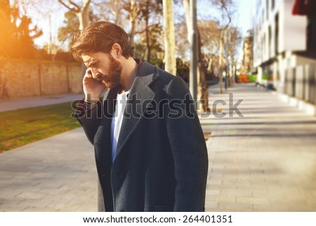 Portrait of handsome adult man talking on cell phone while standing in ...: http://www.shutterstock.com/s/serious phone call/search.html