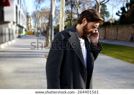 Portrait of handsome adult man talking on cell phone while standing in the city street, business man have conversation, stylish hipster using cellphone at sunny evening outdoors - stock photo