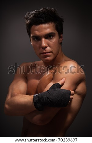Portrait of handsome adult man with big muscles on dark background - stock photo