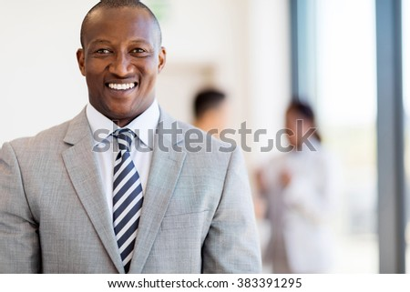 portrait of handsome african american businessman in office - stock photo
