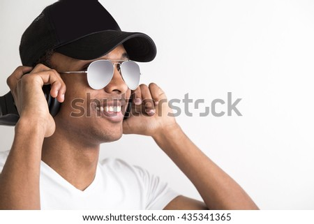 Portrait of handsome african american guy in cap and sunglasses listening to music with headphones on light background - stock photo
