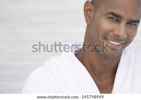 Portrait of handsome African American man in bathrobe smiling - stock photo