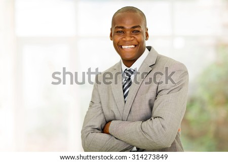 portrait of handsome african businessman with arms folded in office