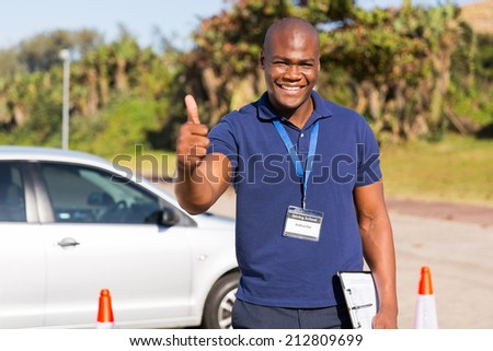 portrait of handsome african driving school instructor giving thumb up - stock photo