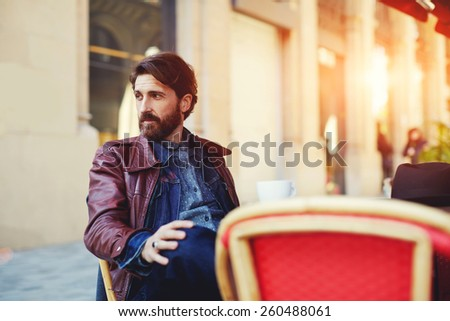 Portrait of handsome and stylish man with beard enjoying a cup of coffee in a coffee shop, adult fashionable hipster having coffee in beautiful cafe terrace at sunny day, flare sun light - stock photo