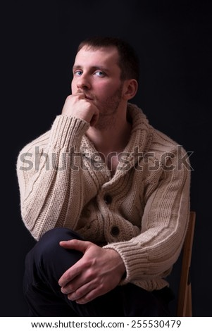 Portrait of handsome and young man in sweater on black background. - stock photo