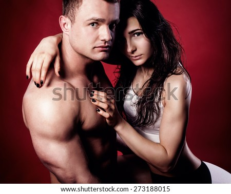 Portrait of handsome athletic couple over red background. Man and woman hugging. - stock photo