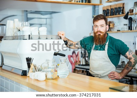 Portrait of handsome barista with beard and tattoo on hands standing near coffee machine in coffee shop - stock photo