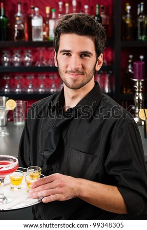 Portrait of handsome barman at bar holding tray with cocktails