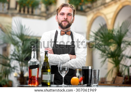 Portrait of handsome barman in uniform with bottles and shaker at the restaurant  - stock photo