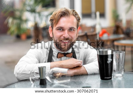 Portrait of handsome barman in uniform with shaker and glasses at the restaurant  - stock photo
