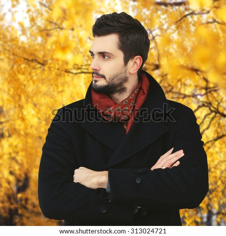 Portrait of handsome bearded man in yellow autumn park - stock photo