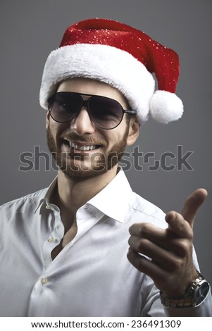 Portrait of handsome bearded young man with christmas hat - stock photo