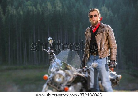 Portrait of handsome biker with beard standing by his custom made cruiser motorcycle. Man is wearing leather jacket sunglasses and blue jeans on a sunny day. Tilt shift lens blur effect - stock photo