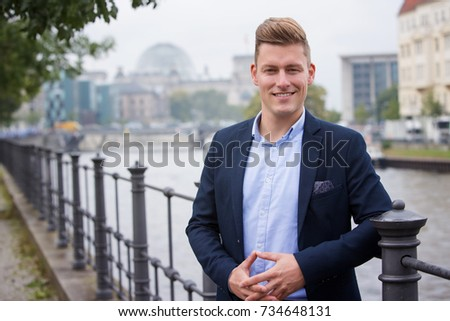 portrait of handsome blond man with german parliament in the background