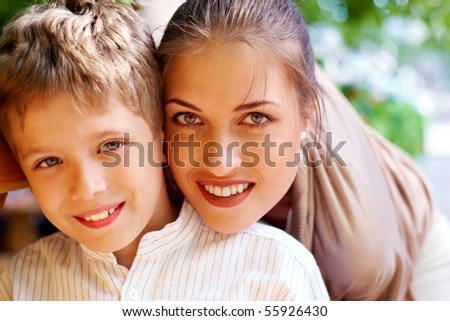 Portrait of handsome boy smiling at camera with his mother near by