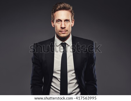 Portrait of handsome business man in dark suit against a grey background