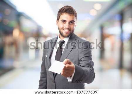 portrait of handsome business man offering his visit card - stock photo