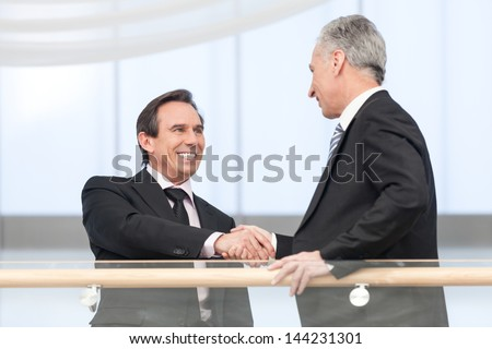 Portrait of handsome business man shaking hands with executive at business center