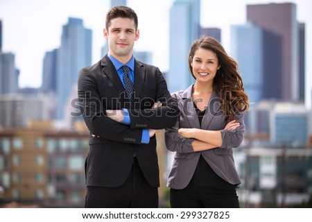 Portrait of handsome businessman and woman confident against downtown skyline buildings  - stock photo