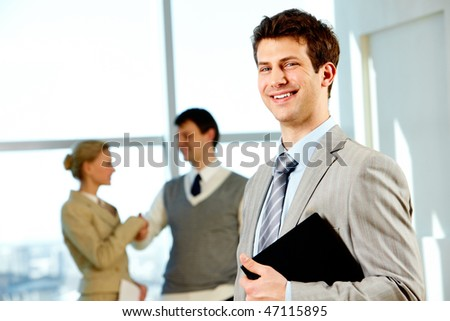 Portrait of handsome businessman holding folder in the office - stock photo