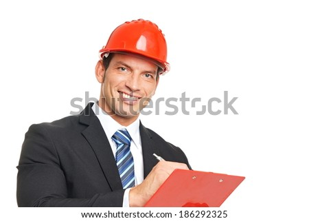 Portrait of handsome businessman in a protective helmet writes some document