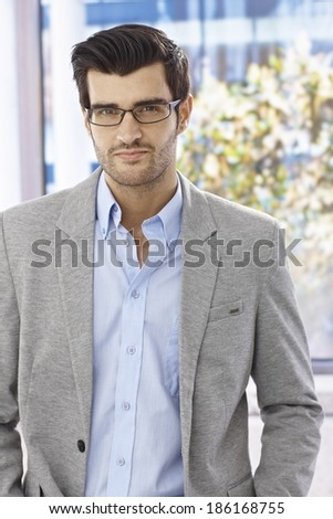 Portrait of handsome businessman in glasses, looking at camera.