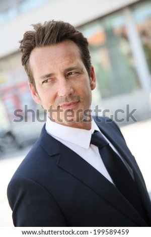 Portrait of handsome businessman in town - stock photo