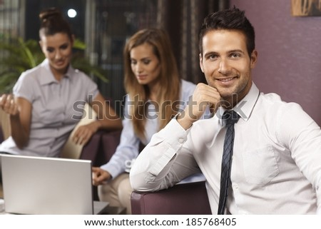 Portrait of handsome businessman sitting on couch, smiling happy, looking at camera. - stock photo