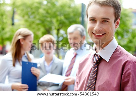 Portrait of handsome businessman smiling at camera in working environment
