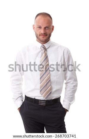 Portrait of handsome businessman standing in shirt and tie with hands in pockets, looking at camera, smiling. - stock photo