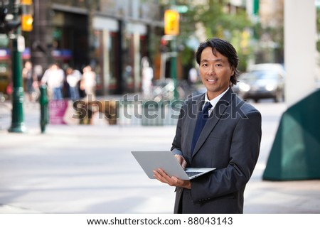 Portrait of handsome businessman using laptop and smiling - stock photo