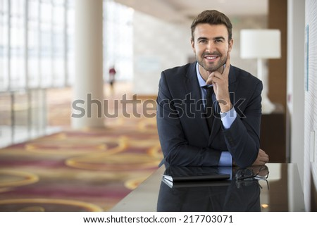 Portrait of handsome businessman using the internet at the hotel lobby - stock photo