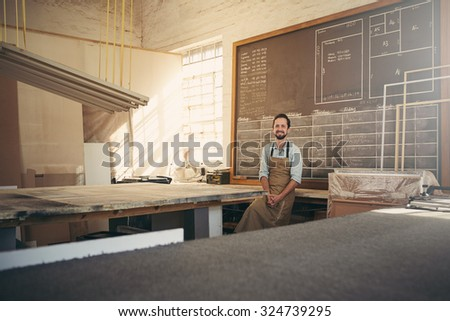 Portrait of handsome carpenter craftsman smiling at the camera while leaning against his workbench in his workshop