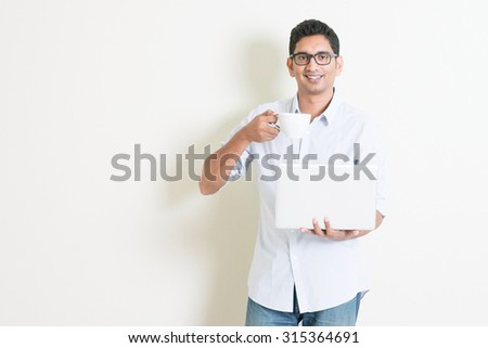 Portrait of handsome casual business Indian guy drinking coffee while using laptop computer, standing on plain background with shadow, copy space at side. - stock photo