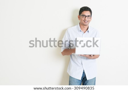 Portrait of handsome casual business Indian guy using laptop computer, standing on plain background with shadow, copy space at side. - stock photo