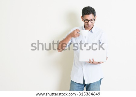 Portrait of handsome casual business Indian man drinking coffee while using laptop computer, standing on plain background with shadow, copy space at side. - stock photo