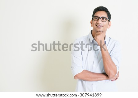 Portrait of handsome casual business Indian man smiling and thinking, eyes looking upwards, standing on plain background with shadow, copy space at side. - stock photo