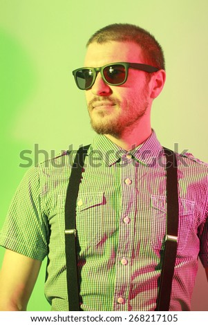 Portrait of handsome casual stylish young man with sunglasses, plaid short sleeve shirt and braces in green and red colored lights - stock photo