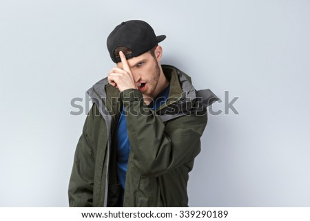 Portrait of handsome caucasian man standing on grey background. Young man with jacket and cap looking at camera - stock photo