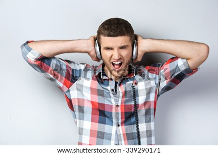 Portrait of handsome caucasian man standing on grey background. Young man with shirt and headphones screaming - stock photo