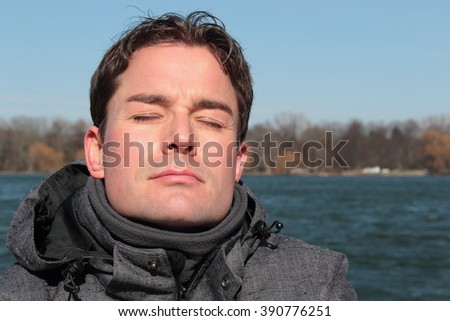 Portrait of handsome caucasian white man with dark hair and closed eyes in a relaxed mood. A blue lake, trees and the cloudless clear blue sky in the background. - stock photo