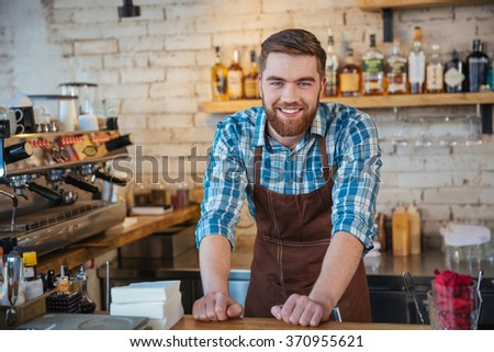 Portrait of handsome cheerful barista smiling and standing in coffee shop  - stock photo