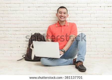 portrait of handsome college student studying using laptop while sitting on the floor - stock photo