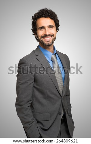 Portrait of handsome confident businessman standing - stock photo