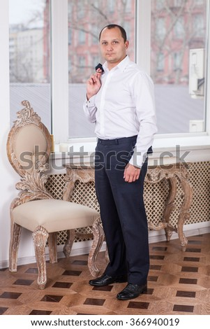 portrait of handsome confident businessman standing in office  - stock photo