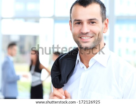 Portrait of handsome confident young businessman, smiling happy, looking at camera - stock photo