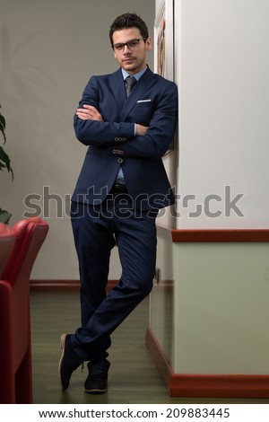 Portrait Of Handsome Confident Young Businessman Standing Arms Crossed - stock photo